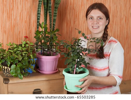 Attractive woman with flowers in the pot at her home