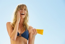 Attractive woman with healthy skin applying sunscreen