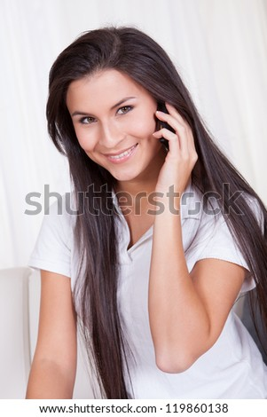Attractive woman with long straight brunette hair smiling at the camera and talking on her mobile phone