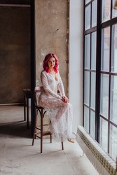 Attractive woman with pink hair in white light dress posing on the bar chair near large window. Lady in gentle lace peignoir sitting in a dark room with concrete floor and walls