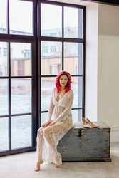 Attractive woman with pink hair in white light dress sitting on the old wooden box near large window. Lady in gentle lace peignoir sitting with bare feet in a room with concrete floor