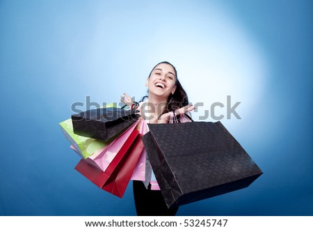 Attractive woman with shopping bags on blue background
