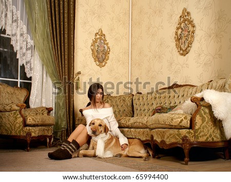 Attractive woman with the labrador dog in the luxury interior
