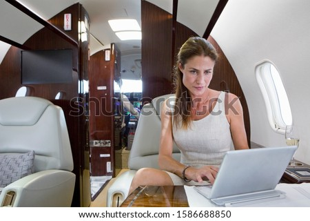 Attractive woman working on digital tablet on private jet