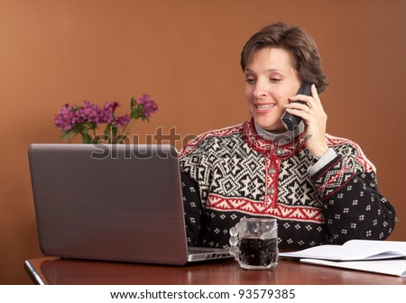 Attractive woman working/shopping from home wearing a winter sweater with a cup of black coffee