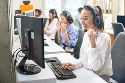 Attractive woman working with customer on hotline support in call center
