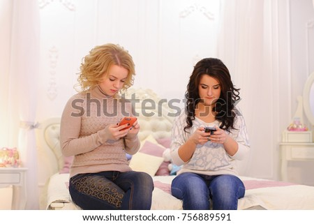 Attractive women look at screens and drive their fingers through gadget sensor and correspond with friends in social networks or read news, laugh and smile at each other. Young women are sitting on