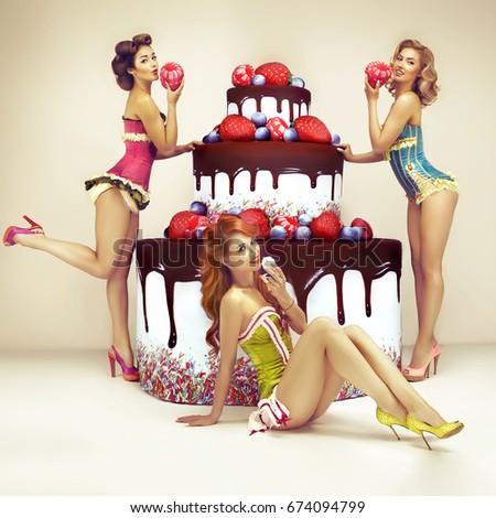 Attractive women posing near big cake. Pinup party. Congratulation concept.