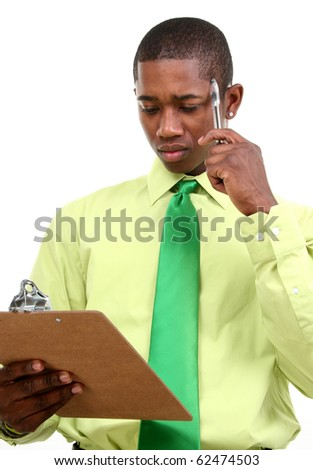 Attractive 25 year old african american man in green shirt, green tie over white background looking concerned at clipboard.
