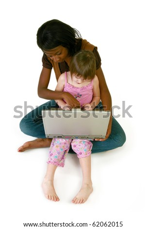Attractive 20 year old African American woman helping 5 year old girl with laptop over white.