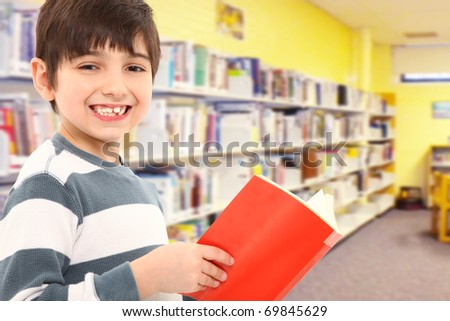 Attractive 7 year old boy with book in school library smiling at camera.