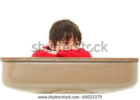 Attractive 7 year old french american boy in school desk over white.