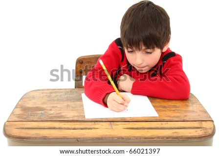 Attractive 7 year old french american boy in school desk over white writing on paper.