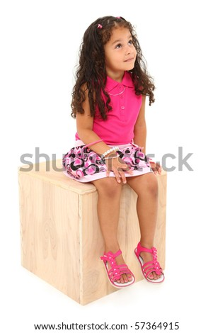 Attractive 3 year old mixed race american girl sitting on wooden block day-dreaming over white background.