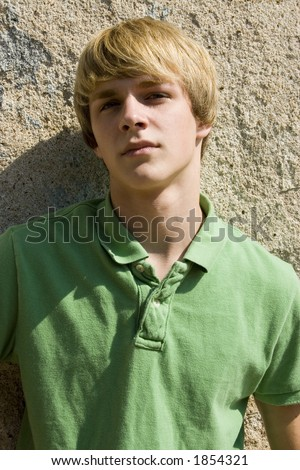 Attractive 15 year old teen boy outside against old wall. - stock