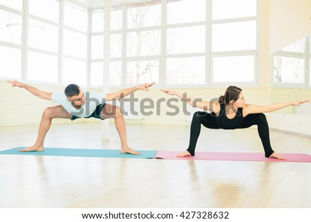 Attractive yoga couple , man and woman, practice exercises in a training hall background. Yoga concept. Stock fotó ©