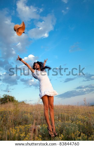 Attractive yong woman is jumping and throwing her hat. Rural evening background.