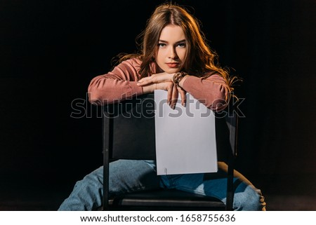 attractive young actress with scenario sitting on chair on stage in theatre Stock fotó ©