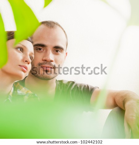Attractive young adult couple sitting close on hardwood floor in home smiling and laughing. Monstera plant on foreground in blur