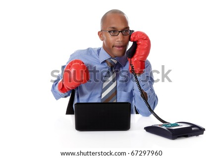 Attractive young African American businessman in office, wearing boxing gloves. Busy talking by telephone. Studio shot. White background.