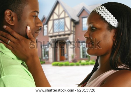 Attractive young african american couple in front of new home.