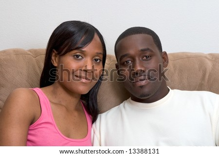 Attractive young african american couple sitting together on their living room couch. Zoomed in Horizontally framed shot. The couple are looking at the camera with a neutral expression.