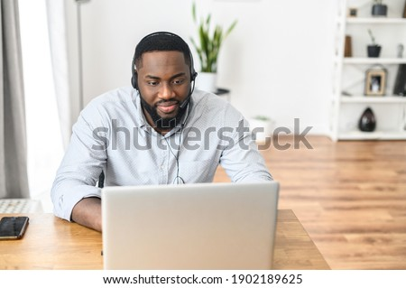 Attractive young African American guy purchasing electronic items online, booking tickets for the conference, buying groceries from the website, a call center operator receiving calls from customers Stok fotoğraf ©