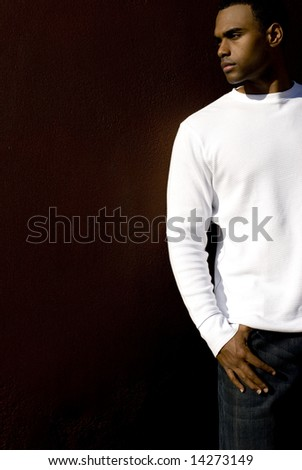 Attractive young African American male playing posing in a white t-shirt and jeans against a solid brown wall.