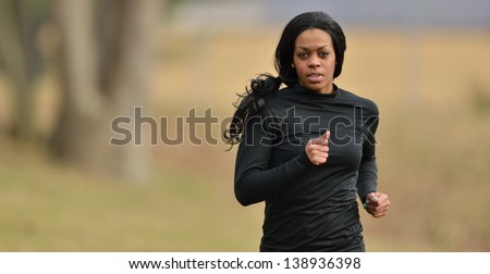 Attractive young African American woman in black fitness gear jogging in a park - cold weather