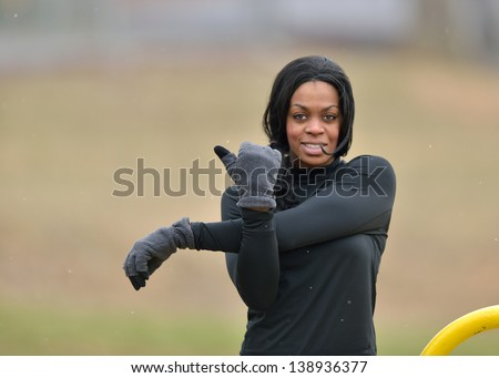 Attractive young African American woman in black fitness gear stretching in a park - cold weather