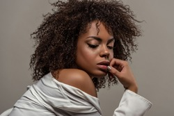 Attractive young african american woman in white shirt touching lips isolated on grey background