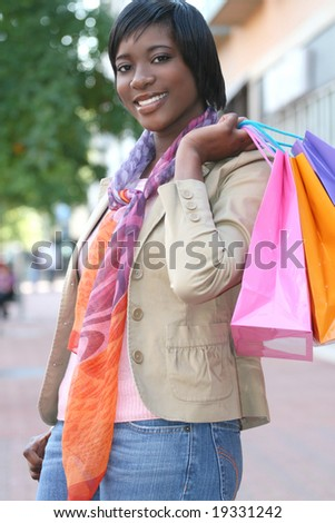 Attractive young African-American woman shopping - shopping  bags, outdoors, street view, suitable for holiday shopping themes, among others