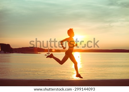 Attractive young African girl athlete running at sunset or sunrise along the beach. Fitness training of runner.