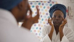 Attractive young African woman applying paper sheet mask on face, looking in mirror in bathroom. Young afro-american lady in bathrobe with towel on head using facial mask after shower