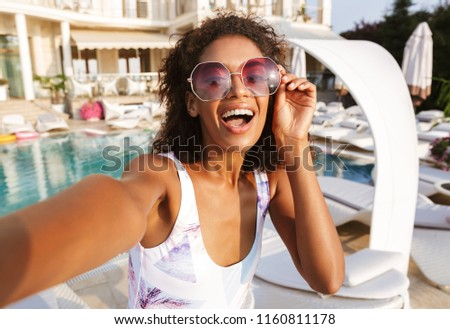 Attractive young african woman in swimsuit taking a selfie while spending good time a swimming pool resort