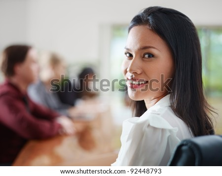 Attractive young Asian business woman smiling and looking over shoulders at business meeting with co-workers.