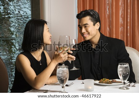 Attractive young Asian couple toast their wine at a restaurant table. Horizontal shot.