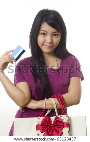 Attractive young Asian girl with shopping bags and credit card