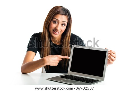 Attractive young asian indian teenage woman, with laptop pointing at screen has advertising space