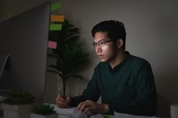 Attractive young asian man sitting on desk table looking at laptop computer in dark late night working feeling serious thinking and determinated at home office in work hard or work load job concept.