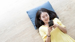 Attractive young Asian woman happy lie down on wooden floor and using mobile phone connect internet for play game online connect with copy space