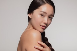 Attractive young asian woman with glowing skin. Korean female with beautiful skin looking at camera against beige background.