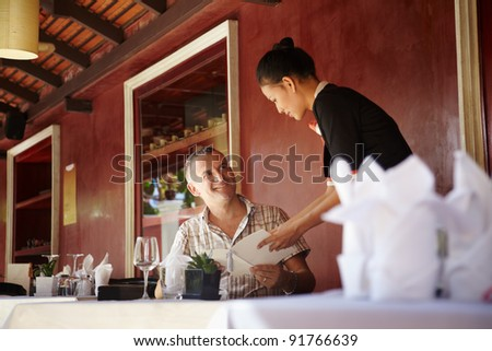 Attractive young asian woman working as waitress in exclusive restaurant and attending customer with menu