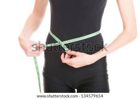 Attractive young athletic and sexy woman measuring size of her waist with a tape measure, isolated on white background.