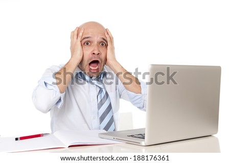 attractive young bald business man screaming in crisis , stress and frustration at computer from pressure watching stocks crash , money and sales loss or technical problems at the office desk