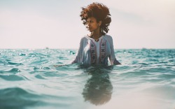 Attractive young black curly girl in traditional African chemise is standing up to the waist in ocean water and looking aside, strong reflection in the bottom, ripples on water surface