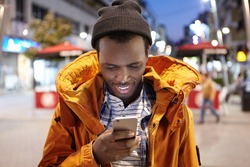 Attractive young black European man in winter clothing typing text message on his mobile, standing in night city setting. Joyful dark-skinned male reading sms from his girlfriend using cell phone