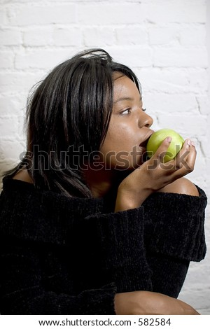 Attractive young black woman eating a green apple