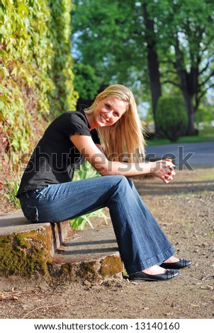 Attractive young blond woman casually dressed smiling at the camera sitting on some stone steps in golden evening light