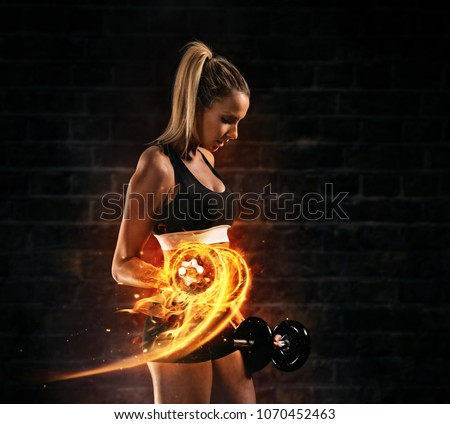 Attractive young blond woman doing bodybuilding, holding fire dumbbells. Concept of hard work and motivation, dark brick wall background. Very high resolution image